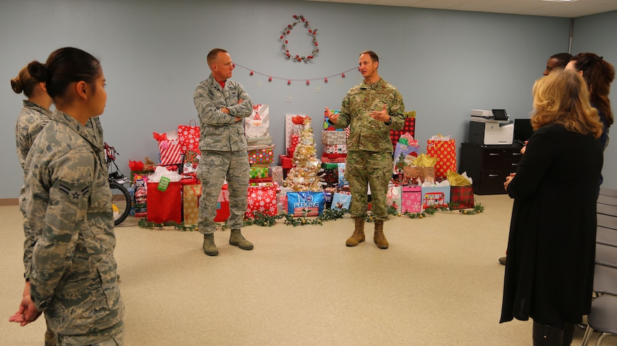 (Center) Col. Julian Cheater, 432nd Wing/432nd Air Expeditionary Wing commander, thanks Airmen volunteers at Creech Air Force Base, Nevada, for their hard work in collecting, wrapping and coordinating delivery of donated gifts for students attending Indian Springs Schools Dec. 14, 2018. Kimberly Guerino, Indian Springs Schools registrar, and Kelly Miles, Indian Springs Schools counselor, accepted the gifts on behalf of their students. (U.S. Air Force photo by Tech. Sgt. Dillon White)