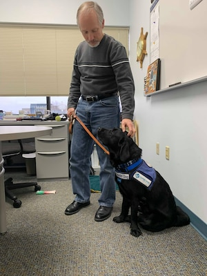 If you step inside Jeff Schafer's office, you'll see an assortment of things you might expect, like a coffee mug and a computer. You may not have anticipated, or even noticed, a service dog-in-training to be lying patiently by Schafer's feet.