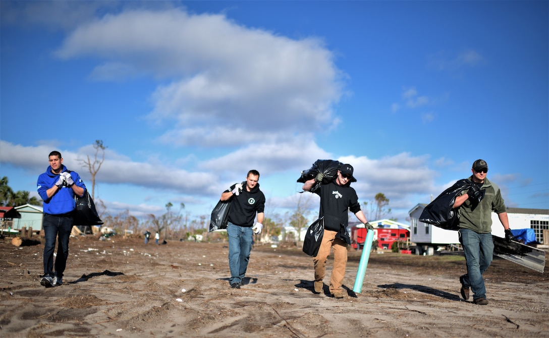 Airman from Tyndall Air Force Base carry bags of debris while carrying bags of trash while cleaning debris from Under the Palms Park in Mexico Beach, Fla., Dec. 16, 2018. Thirty nine volunteers from Tyndall and Eglin Air Force Bases came together to help clean Mexico Beach, one of the communities hit the hardest by Hurricane Michael.  The volunteers were able to clean up more than 40 cubic yards of debris within four hours. (U.S. Air Force photo by Tech. Sgt. Sara Keller)