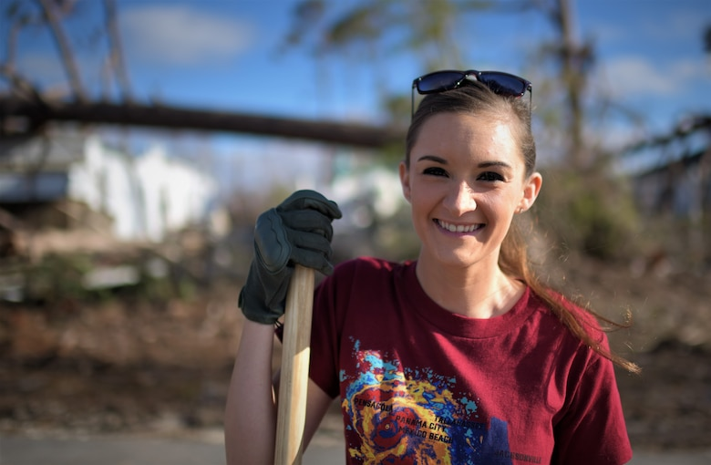 Senior Airman Megan Timbers, 325th Force Support Squadron readiness and plans and event coordinator, stands in front of a broken tree line at Under the Palms Park in Mexico Beach, Fla., Dec. 16, 2018. Timbers helped recruit volunteers from Tyndall and Eglin Air Force Bases to come together to help clean Mexico Beach, one of the communities hit the hardest by Hurricane Michael.  The volunteers were able to clean up more than 40 cubic yards of debris within four hours. (U.S. Air Force photo by Tech. Sgt. Sara Keller)