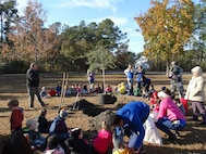 Keith Thompson, the conservation program manager with the 628th Civil Engineer Squadron, speaks to children at the Joint Base Charleston Naval Weapons Station Child Development Center about the importance of trees in our communities during the base's Arbor Day celebration, held annually on Dec. 7.