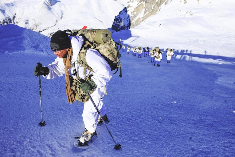 Soldiers climb a steep snowy mountain slope