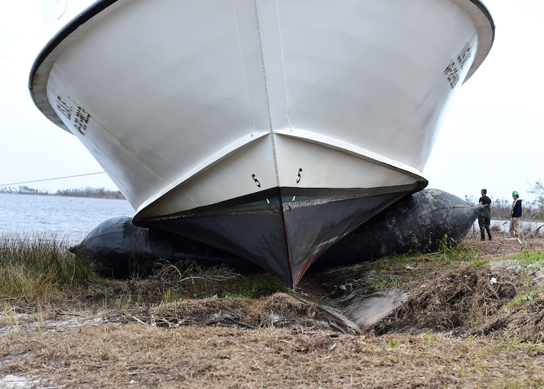 A beached U.S. Air Force Missile Retriever Ship is raised from the ground by inflatable bladders near Tyndall Air Force Base, Fla., Dec. 13, 2018. The strong winds of Hurricane Michael caused the vessel to run aground over two months ago. The Missile Retriever ship is responsible for the location and recovery of Subscale Aerial Targets in the Gulf of Mexico W151 Live-Fire Range. MR's also conduct launch and recovery corridor clearance operations for both SSAT and Full-scale Aerial Target Missions. (U.S. Air Force photo by Senior Airman Isaiah J. Soliz)