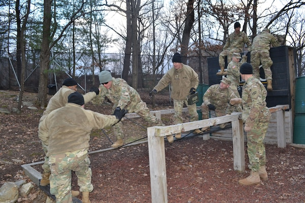 """Officers and noncommissioned officers assigned to the 642nd  Aviation Support Battalion, New York Army National Guard, work  together on the """"river crossing"""" obstacle at the United States Military Academy Leadership Reaction Course  at West Point, N.Y., on Dec. 8 2018. The training was designed so 642nd senior leaders could test their problem solving and decision-making skills while learning how to work better  together."""
