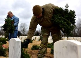 A person in uniform lays a wreath of the headstone of a service member.