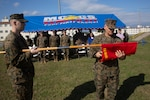 Capt. Benjamin Barr, right, unfurls the company colors, presented by Gunnery Sgt. Derek Carlson, during the III Marine Expeditionary Force Information Group Communication Strategy and Operations Company activation of command ceremony on Camp Hansen, Okinawa, Japan, Dec. 14, 2018. III MIG COMMSTRAT co. provides imagery production support to III MEF, 3D Marine Expeditionary Brigade, the 31st Marine Expeditionary Unit, the MIG Headquarters, and MIG major subordinate units.