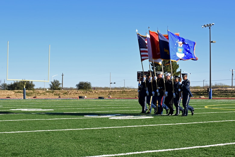 """Joint Service Color Guard marches onto the field to present the colors during the Army-Navy game at the Mathis Fitness Center field on Goodfellow Air Force Base, Texas, Dec. 14, 2018. After presenting the colors, there was the playing of """"retreat"""" and the """"national anthem"""" followed by the coin flip to begin the game. (U.S. Air Force photo by Airman 1st Class Zachary Chapman/Released)"""