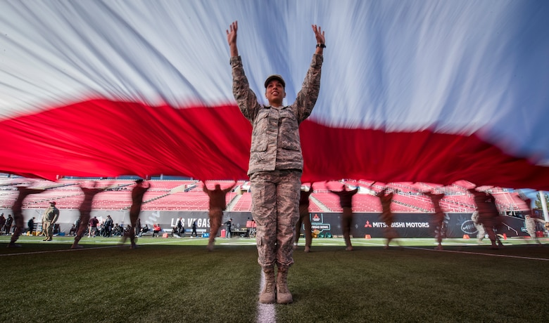 Airman 1st Class Ashley Libby, an aerospace medical technician assigned to the 99th Medical Operations Squadron at Nellis Air Force Base, Nevada, raises her arms to keep the American flag off the ground during the 2018 Las Vegas Bowl opening ceremony at Sam Boyd Stadium in Las Vegas, Dec. 15, 2018. The half-ton flag required more than 200 Airmen to carry it. (U.S. Air Force photo by Senior Airman Andrew D. Sarver)