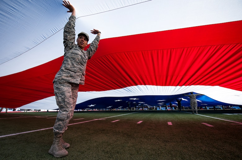 Airman 1st Class Ashley Libby, an aerospace medical technician assigned to the 99th Medical Operations Squadron at Nellis Air Force Base, Nevada, holds up a section of a half-ton American flag during the 2018 Las Vegas Bowl opening ceremony at Sam Boyd Stadium in Las Vegas, Dec. 15, 2018. More than 200 Airmen volunteered to carry the flag. (U.S. Air Force photo by Senior Airman Andrew D. Sarver)