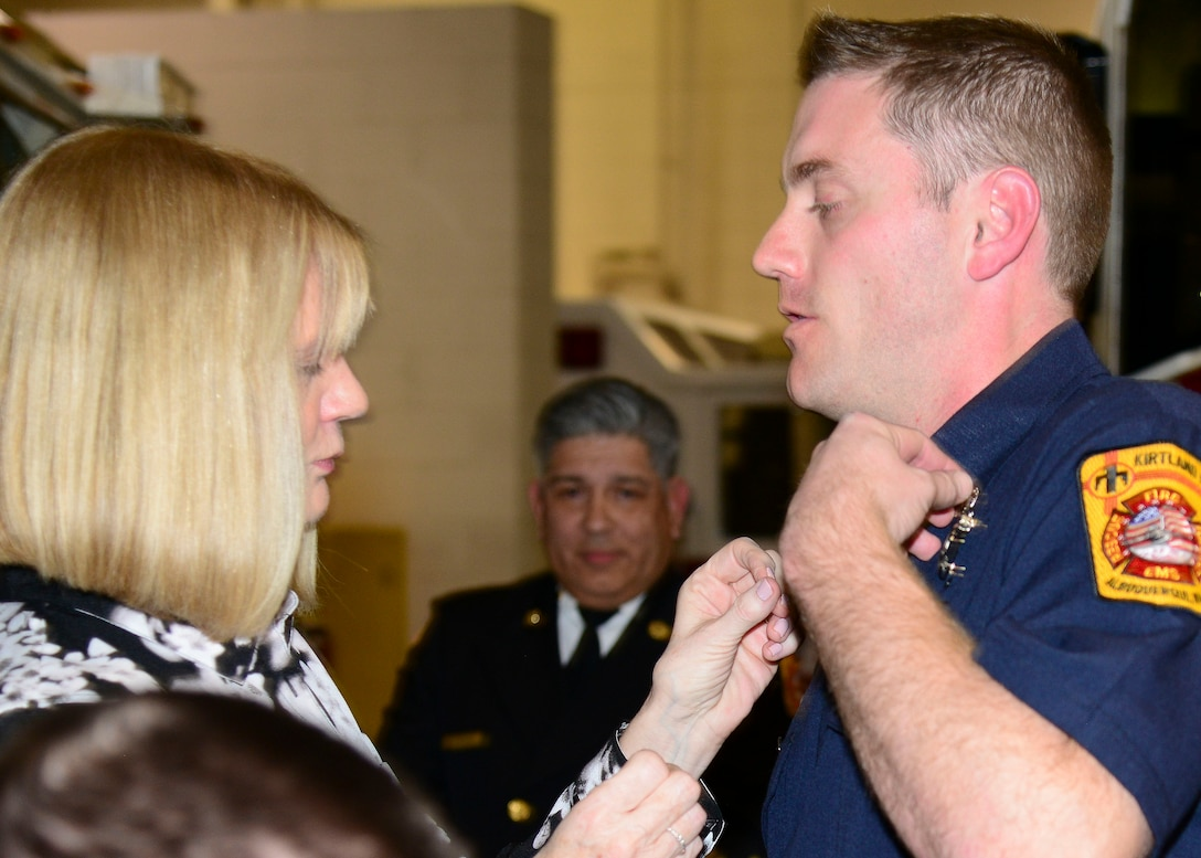 Lynda Davis pins her son Christopher Davis during the Kirtland AFB Fire and Emergency Services Training Academy graduation here Dec. 14. The graduates underwent eight weeks of training completing the first iteration conducted at Kirtland for 14 years. (U.S. Air Force photo by Jessie Perkins)