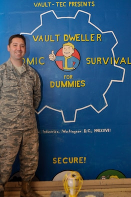 """Tech. Sgt. Raymond Kiser of the 320th Missile Squadron stands next to the """"Fallout"""" themed mural he painted inside a missile alert facility elevator shaft way at F.E. Warren Air Force Base, Wyo., Aug. 21, 2018."""