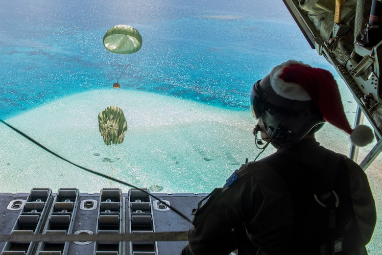 Royal Australian Air Force SGT Karl Penny, 37th Squadron C-130J Super Hercules loadmaster out of RAAF Base Richmond, Australia, looks out as the parachute for a Low-Cost, Low-Altitude bundle carries humanitarian aid down to the atoll of Kapingamarangi, Federated States of Micronesia (FSM), during Operation Christmas Drop 2018, Dec. 13, 2018. Every December U.S. Air Force crews from Yokota Air Base, Japan team up with the Japan Air Self-Defense Force (Koku Jietai) and RAAF to airdrop supplies to the Commonwealth of the Northern Marianas, FSM, and the Republic of Palau. (U.S. Air Force photo by Senior Airman Matthew Gilmore)