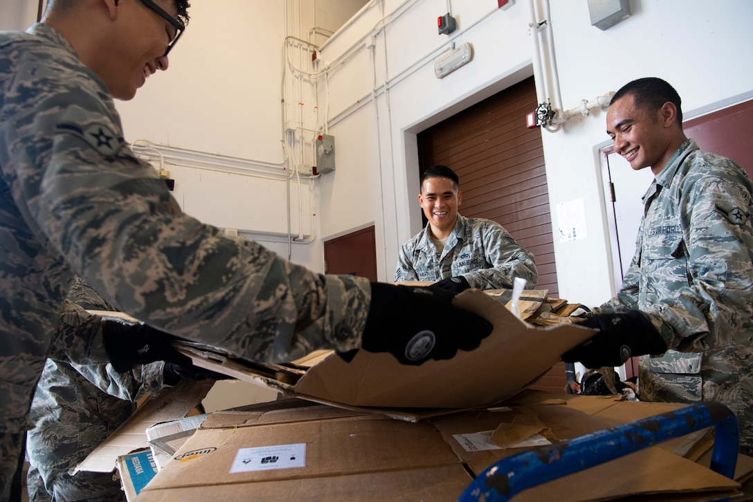 U.S. Air Force Airman Willy Hong (left to right), Staff Sgt. Michael Penaso and Airman Brandon Phillip, all air transportation specialist with the U.S. Air Force Reserve's 44th Aerial Port Squadron, break down empty donation boxes Dec. 8, 2018, during Operation Christmas Drop at Andersen Air Force Base, Guam. Operation Christmas Drop is a U.S. Air Force-led trilateral training event that includes air support from the Japanese Air Self Defense Force and Royal Australian Air Force to airdrop supplies to the Commonwealth of the Northern Marianas, Federated States of Micronesia, and the Republic of Palau. (U.S. Air Force photo by Jerry R. Bynum)