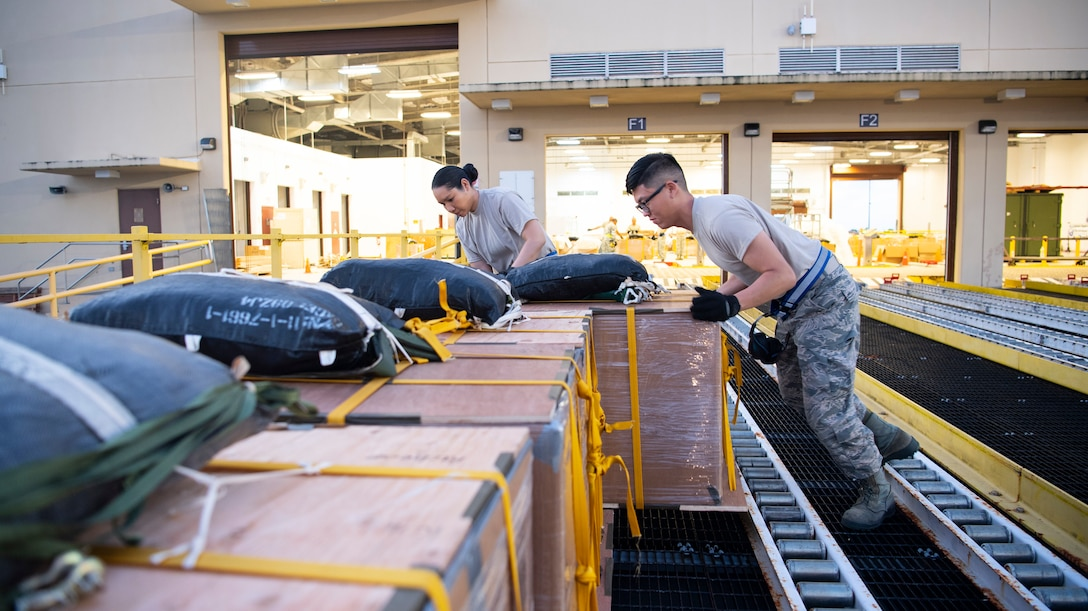 U.S. Air Force Senior Airman Yvonne Manglona and Airman Willy Hong, both air transportation specialist with the U.S. Air Force Reserve's 44th Aerial Port Squadron, preposition airdrop bundles ready for transportation out to awaiting aircraft Dec 9, 2018, during Operation Christmas Drop at Andersen Air Force Base, Guam. Operation Christmas Drop is a U.S. Air Force-led trilateral training event that includes air support from the Japanese Air Self Defense Force and Royal Australian Air Force to airdrop supplies to the Commonwealth of the Northern Marianas, Federated States of Micronesia, and the Republic of Palau. (U.S. Air Force photo by Jerry R. Bynum)