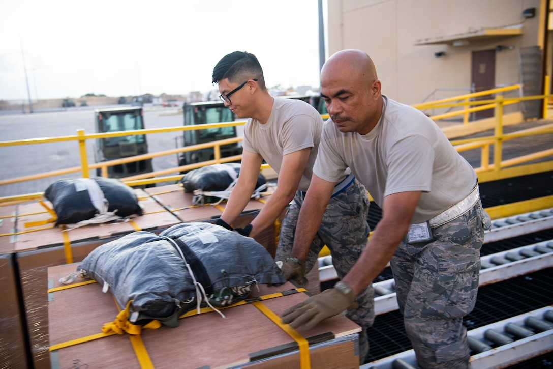 U.S. Air Force Airman Willy Hong (left to right) and Master Sgt. Rene Molinos, both air transportation specialist with the U.S. Air Force Reserve's 44th Aerial Port Squadron, preposition airdrop bundles ready for transportation out to awaiting aircraft Dec 9, 2018, during Operation Christmas Drop at Andersen Air Force Base, Guam. Operation Christmas Drop is a U.S. Air Force-led trilateral training event that includes air support from the Japanese Air Self Defense Force and Royal Australian Air Force to airdrop supplies to the Commonwealth of the Northern Marianas, Federated States of Micronesia, and the Republic of Palau. (U.S. Air Force photo by Jerry R. Bynum)