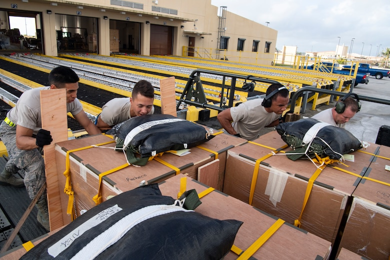 U.S. Air Force Airman 1st Class Joshua San Agustin (left-right), Airman Giovanni Manglona, Airman Brandon Phillip and Master Sgt. David Popp, all air transportation specialist with the U.S. Air Force Reserve's 44th Aerial Port Squadron, load and secure airdrop bundles onto a Tunner 60K aircraft loader for transportation out to awaiting aircraft Dec. 11, 2018, during Operation Christmas Drop at Andersen Air Force Base, Guam. Operation Christmas Drop is a U.S. Air Force-led trilateral training event that includes air support from the Japanese Air Self Defense Force and Royal Australian Air Force to airdrop supplies to the Commonwealth of the Northern Marianas, Federated States of Micronesia, and the Republic of Palau. (U.S. Air Force photo by Jerry R. Bynum)