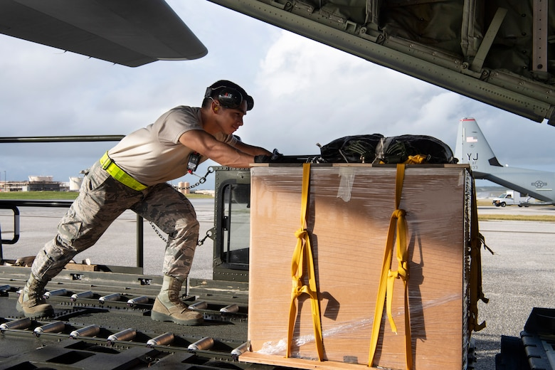 U.S. Air Force Airman 1st Class Joshua San Agustin, an air transportation specialist with the U.S. Air Force Reserve's 44th Aerial Port Squadron, loads a U.S. Air Force C-130J Hercules Dec. 11, 2018, with an airdrop bundle during Operation Christmas Drop at Andersen Air Force Base, Guam. Operation Christmas Drop is a U.S. Air Force-led trilateral training event that includes air support from the Japanese Air Self Defense Force and Royal Australian Air Force to airdrop supplies to the Commonwealth of the Northern Marianas, Federated States of Micronesia, and the Republic of Palau. (U.S. Air Force photo by Jerry R. Bynum)