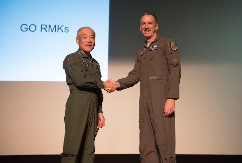 Southwestern Air Defense Force Lt. Gen. Hiroshi Kaminotani, SWADF commander, left, and U.S. Air Force Brig. Gen. Case Cunningham, 18th Wing Commander, right, shake hands at the start of the Alliance Coordination Mechanism Sept. 25, 2018, at Kadena Air Base, Japan. Both countries worked to strengthen cooperation by mutually sharing information and enhancing situational awareness.