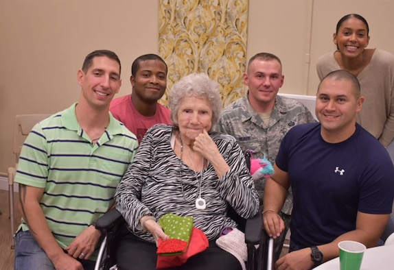 (Left to right) Master Sgt. Watson, Tech. Sgt. Sylvester, Tech. Sgt. Ruark, Master Sgt. Benavides and Senior Airman. Gilliard pose with a resident after a round of bingo at the Morningside Manor Senior Living Community, San Antonio, Texas.
