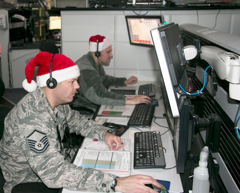 New York Air National Guards Master Sgt. Shane Reid, front, and Tech. Sgt. Brady King, both of the 224th Air Defense Squadron, train for upcoming Santa tracking operations at the Eastern Air Defense Sector in Rome. A headquarters unit of the North American Aerospace Defense Command (NORAD), EADS supports the NORAD Tracks Santa operation every year.