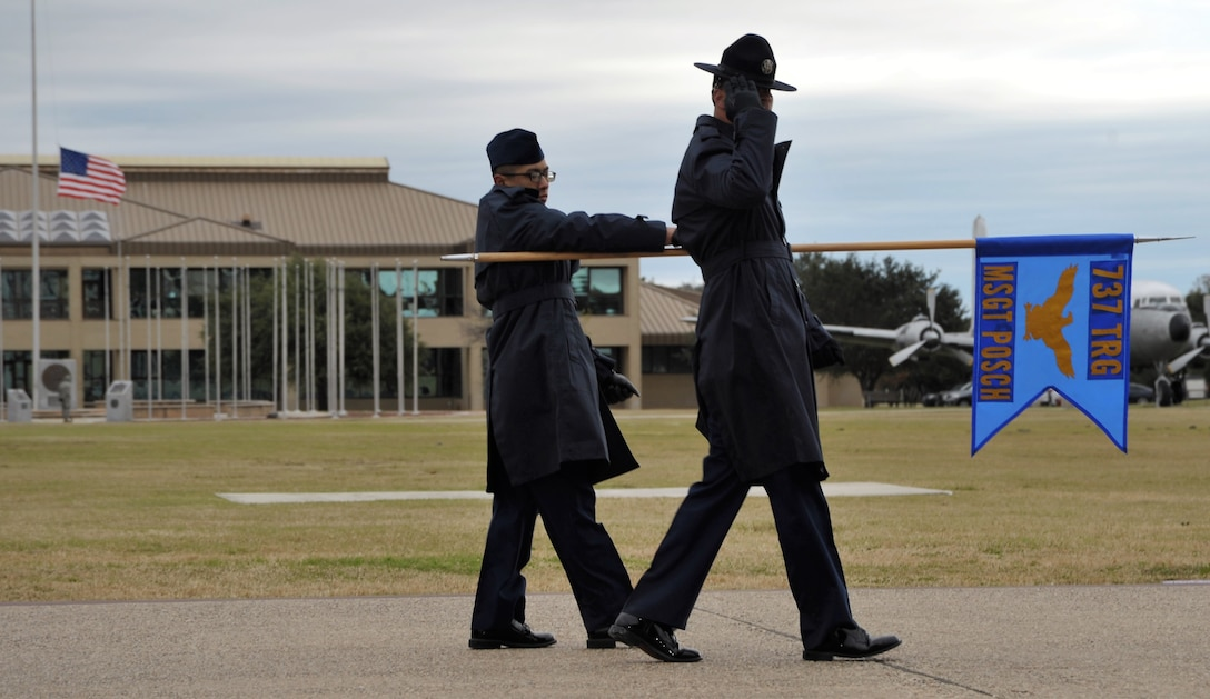 A 433rd Training Squadron basic military training instructor and trainee salute the reviewing official and distinguished guests during the Dec. 14 BMT graduation at Joint Base San Antonio-Lackland, Texas. This flight was named in honor of fallen Reserve Citizen Airmen Pararescueman Master Sgt. William Posch.  (U.S. Air Force photo by Debbie Gildea)