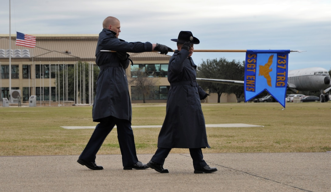 A 433rd Training Squadron basic military training instructor and trainee salute the reviewing official and distinguished guests during the Dec. 14 BMT graduation at Joint Base San Antonio-Lackland, Texas. This flight was named in honor of fallen Reserve Citizen Airmen Pararescueman Staff Sgt. Carl Enis.  (U.S. Air Force photo by Debbie Gildea)