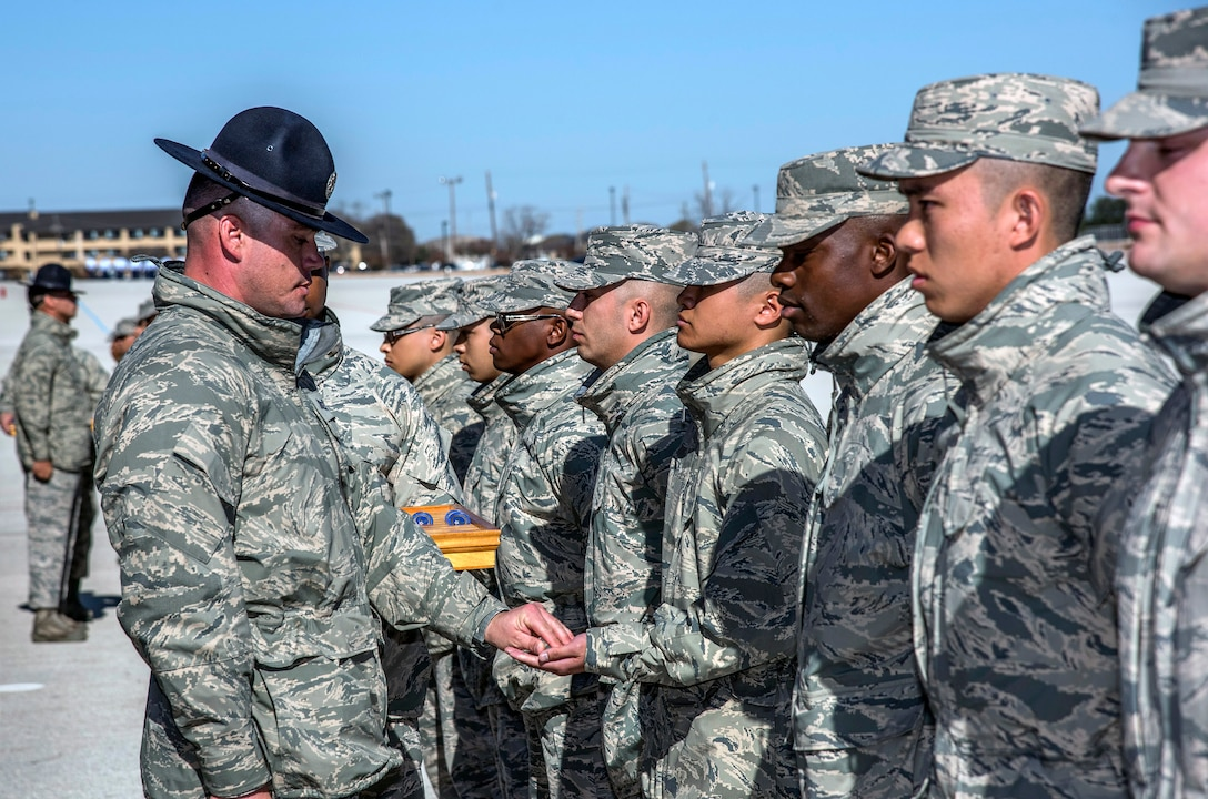 Military Training Instructor Tech. Sgt. Prentiss Carver, 433rd Training Squadron Reserve Citizen Airman, presents the Airman's coin to one of his trainees during the Dec. 13 Airman's coin presentation ceremony at Joint Base San Antonio-Lackland. The ceremony occurs the day before basic military training graduation and symbolizes that the trainee has completed BMT requirements and has earned the right to be called Airman. (U.S. Air Force photo by Johnny Saldivar)