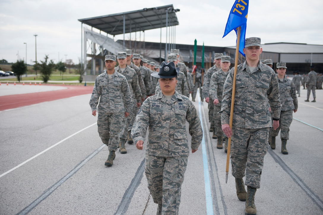 Military Training Instructor Tech. Sgt. Christina Rapolla, 433rd Training Squadron Reserve Citizen Airman, leads her flight in drill during the early weeks of basic military training. Attention to detail, discipline and teamwork learned at this stage enabled trainees to succeed and graduate during ceremonies held here Dec. 14. (U.S. Air Force photo by Sy Pinthong)