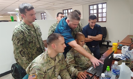 Ben Loader, Department of Homeland Security (DHS) personnel, middle, and Lt. Marcus Guevara, right, observe Staff Sgt. Asiel Conde, 600 Cyber Protection Team, center, setting up network tools at Soto Cano Air Base, Dec. 2018.