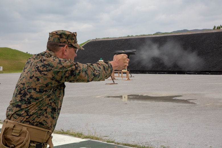 A U.S. Marine competing in the Far East Marksmanship Competition fires a round at Range 1 on Camp Hansen, Okinawa, Japan Dec. 13, 2018. The M9 is the standard issue pistol for the Marine Corps and fires a 9mm round.