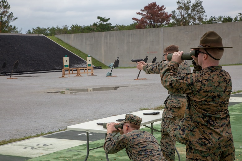 A U.S. Marine shooter and spotters assess the target in the Team Pistol Match finals at Range 1 on Camp Hansen Dec. 13, 2018. Marine Corps Shooting Teams members verified the hits of the shooter.