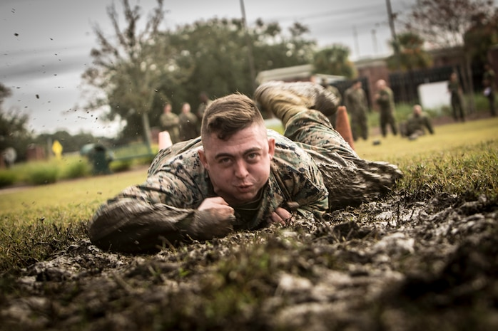 Cpl. Darrell Reynolds, the fiscal chief with 4th Marine Logistics Group, Marine Forces Reserve, low crawls during the maneuver under fire portion of the Combat Fitness Test at Marine Corps Support Facility New Orleans, Dec. 14, 2018. The CFT is an annual fitness assessment comprised of a simulated movement to contact, which is an 880-meter sprint; 2 minutes of 30-pound ammo can lifts, and a maneuver under fire, which is a timed 300-yard shuttle run of combat-related tasks. (U.S. Marine Corps photo by Cpl. Tessa D. Watts)