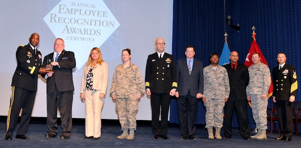 DLA Director and DLA Navy Senior Enlisted Leader present a group award to a team of eight people.
