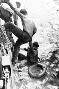 IMAGE: Oct. 25, 1944: American survivors of the battle are rescued by a U.S. Navy ship on Oct. 26, 1944. Some 1,200 survivors of USS Gambier Bay (CVE-73), USS Hoel (DD-533), USS Johnston (DD-557) and USS Samuel B. Roberts (DE-413) were rescued during the days following the action. Photographed by U.S. Army Private William Roof/Photograph from the Army Signal Corps Collection in the U.S. National Archives