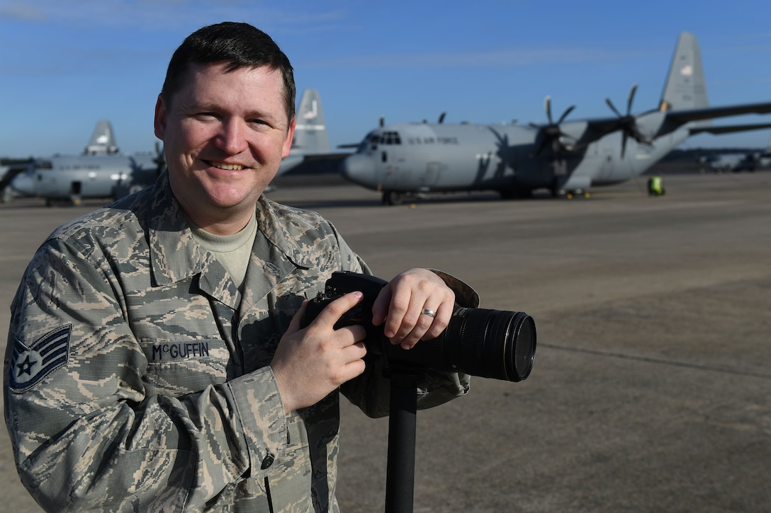A man poses with a camera in front of a C-130.