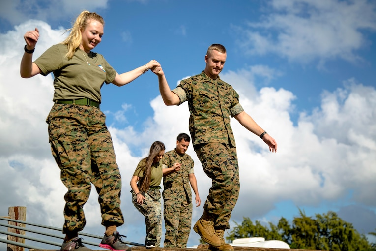 Two Marines escort their spouses on an obstacle course.