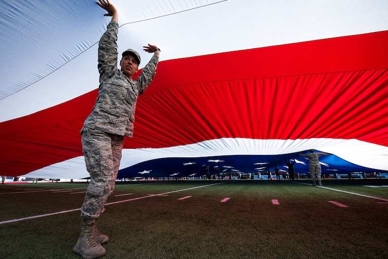 An airman holds her arms up on a football field, under giant red and white stripes of a U.S. flag.