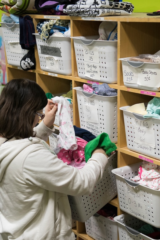 Melody Undiener, wife of U.S. Air Force Staff Sgt. Johnathan Undiener, a 732d Aircraft Maintenance Unit crew chief, sifts through baby clothes at the Fort Richardson Thrift Shop, Joint Base Elmendorf-Richardson, Alaska Dec. 12, 2018. The store is open to all branches of active duty, the National Guard, Reserve, retired military personnel, their dependents and anyone with access to JBER.