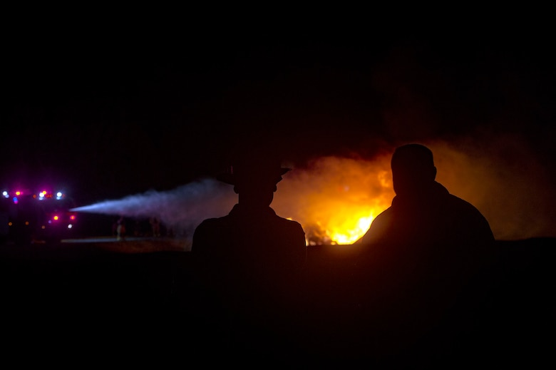 Valdosta Fire Department members watch the 23d Civil Engineer Squadron extinguish a simulate aircraft fire during live-fire training, Nov. 29, 2018, at Moody Air Force Base, Ga. The units strengthened their alliance and firefighting capabilities by jointly extinguishing a simulated aircraft fire to maintain their Airport Rescue and Firefighting proficiency. (U.S. Air Force photo by Senior Airman Greg Nash)
