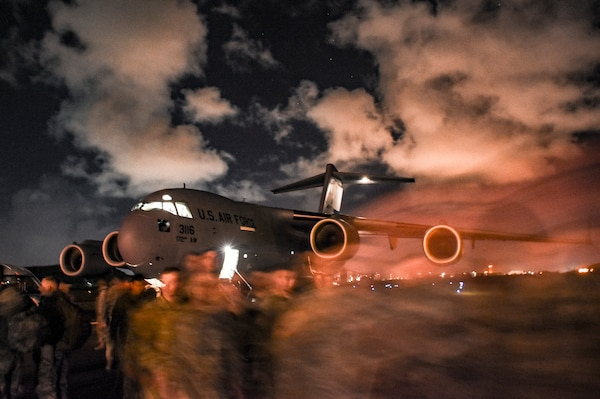 Soldiers passing in the night before a dimly lit C17 from the 172nd Air Wing of the Mississippi National Guard, are arriving for a training exercise in the Virgin Islands to provide support to civil authorities in a post hurricane training scenario.