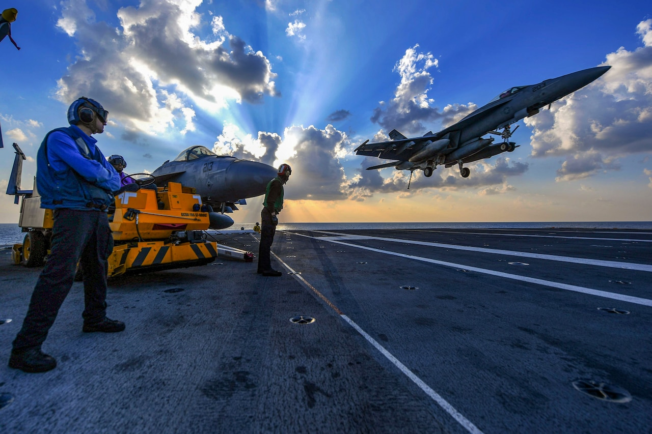 An aircraft comes in for a landing on the flight deck of a navy vessel.