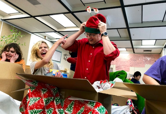 Master Sgt. Michael Johnson, 67th Aerial Port Squadron, helps Shayla unpack a box of gifts during a Christmas party at Mound Fort Junior High in Ogden