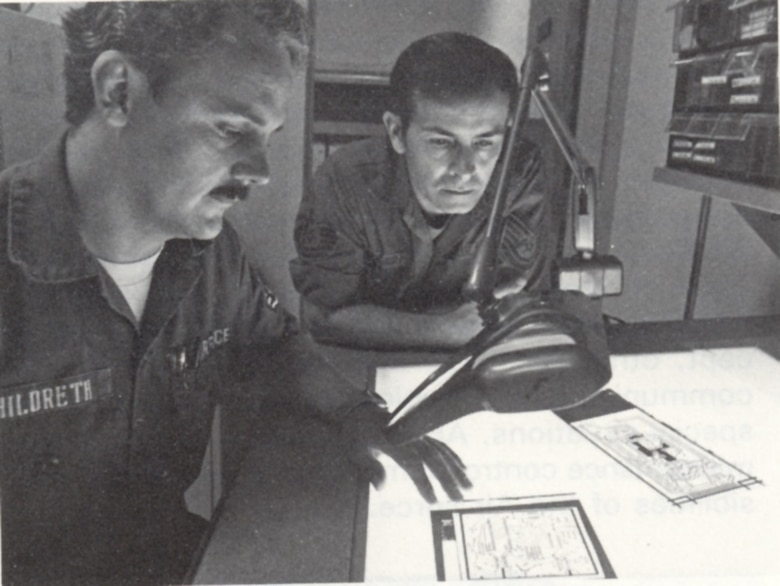 Members of the 1842nd Electronics Engineering Group review circuit board negatives, Scott AFB, Illinois.