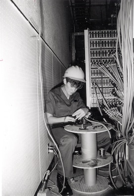 "Sharnee Riley, 1837th Engineering Installation Squadron, uses an Amphanol ""Amp-Champ"" crimper to terminate a connector on one of the multitude of 25-pair cables installed at the control site as part of the Scope Signal III installation to modernize Giant Talk, the Strategic Air Command's world-wide command and controls network, Clark AB, Philippines."