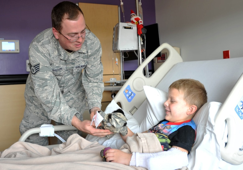 Staff Sgt. Jeremy Robinson, 373rd Training Squadron, Det. 8 KC-46 Pegasus and KC-135 Stratotanker hydraulic instructor, hands a military teddy bear to a child Dec. 18, 2018, at Wesley Children's Hospital. The members wanted to spread some cheer to children right before the holidays to brighten their mood and make the stay at the hospital a little better. (U.S. Air Force photo by Staff Sgt. David Bernal Del Agua)