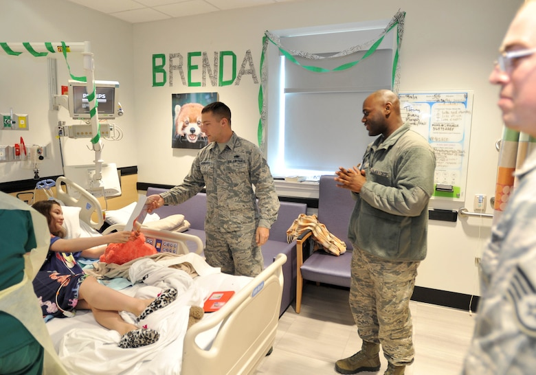Staff Sgt. Cody Verbanac, 373rd Training Squadron, Det. 8 KC-46 Pegasus fuel systems instructor, hands a puzzle to a child Dec. 18, 2018, at Wesley Children's Hospital. The maintenance Airmen spread some holiday cheer throughout the hospital to the children having to stay there. (U.S. Air Force photo by Staff Sgt. David Bernal Del Agua)