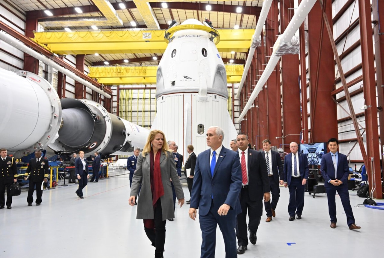 Vice President Mike Pence walks with group of people in front of a space capsule.