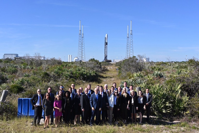 Vice President Mike Pence stands with a large group of people in front of a space satellite.