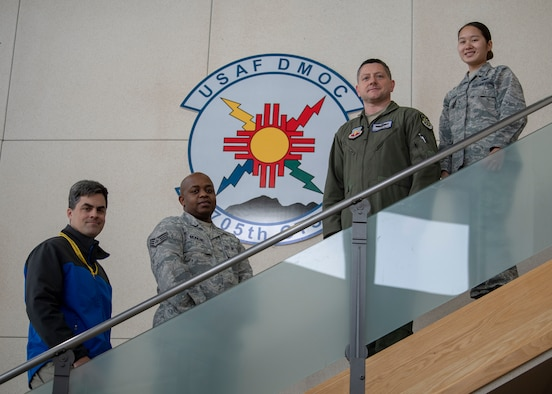 From left to right, Ray Renfrow, Science Application International Corporation modeling and simulation engineer; Staff Sgt. Anthony Munene, 705th Combat Training Squadron commander support staff NCO in charge; Master Sgt. Charles Phillips, 705th CTS superintendent; and 1st Lt. Arthittiya Mongkolsombat, 705th CTS executive officer pose for a photo at Kirtland Air Force Base, N.M., Dec. 11, 2018. These individuals each took part in saving the life of Maj. Myles Cheatum, 552nd Air Control Wing plans and programs deputy director, who went into cardiac arrest while TDY at Kirtland AFB. (U.S. Air Force photo by Staff Sgt. J.D. Strong II)