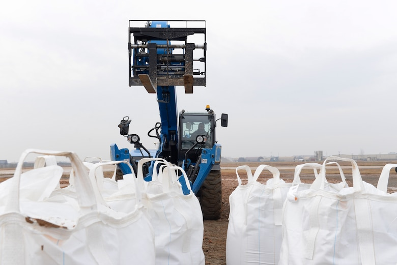 A U.S. Air Force 8th Civil Engineer Squadron forklift operator prepares to lift bags of quick drying concrete mix during Rapid Airfield Damage Repair training at Kunsan Air Base, Republic of Korea, Dec. 6, 2018. 8th CES teams filled large holes with concrete to test their capabilities to quickly repair runway damage in a variety of scenarios. (U.S. Air Force photo by 1st Lt. Madeline Krpan)